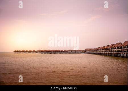 Exotic over water bungalows at a tropical island resort. Beautiful sunset sky, tranquil sea, romantic getaway destination - Stock Photo
