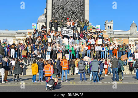 Group of teenagers school children kids miss school to strike & protest on climate change wave placard & chant from  Nelsons Column London England UK - Stock Photo