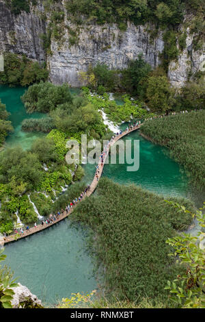 The beautiful and stunning Plitvice Lake National Park, Croatia, an aerial shot of a broad walk with people in between two lake - Stock Photo