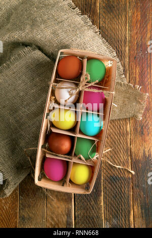 Multicoloredeaster eggs in wooden box on burlap on old wooden table. - Stock Photo