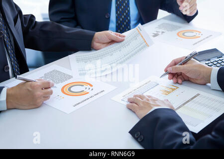 Businessmen are deeply reviewing a financial reports for a return on investment or investment risk analysis.