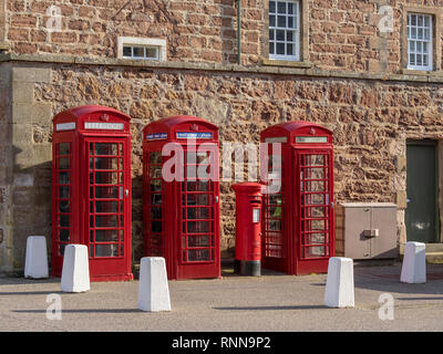 Three British red telephone boxes or kiosks and one red post box or pillar box, Fort George, near Inverness, Scotland - Stock Photo