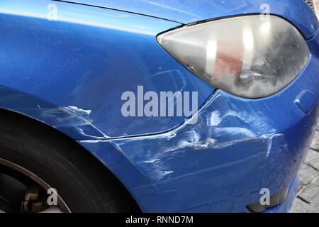 Generic car with scratched paint on front wing. Minor accident result - fender bender. - Stock Photo