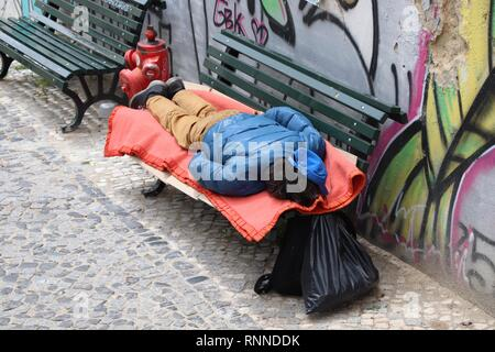 LISBON, PORTUGAL - JUNE 4, 2018: Homeless person sleeping rough in Lisbon, Portugal. There are estimated 3000 homeless persons in Lisbon. - Stock Photo
