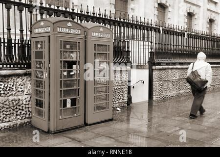London, United Kingdom - telephone boxes in wet rainy weather. Sepia tone - filtered retro style monochrome photo. - Stock Photo