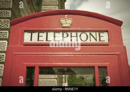 London, United Kingdom - red telephone box close-up. Cross processing color tone - filtered retro style. - Stock Photo