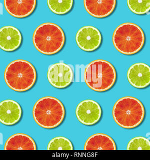 Vibrant red orange and green lime lemon slices pattern on turquoise color background. Minimal flat lay top view food texture - Stock Photo
