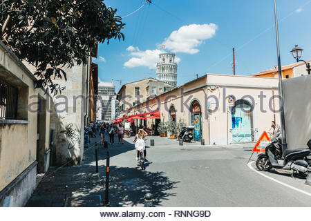 Pisa, Italy - May, 17, 2017: A view of the leaning tower of pisa in the distance from the back streets. - Stock Photo