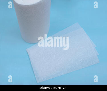 Soft strong and absorbent paper towel isolated on blue under pad. - Stock Photo