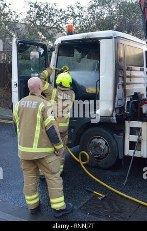 Firefighters tackling a lorry fire on a residential street - Stock Photo