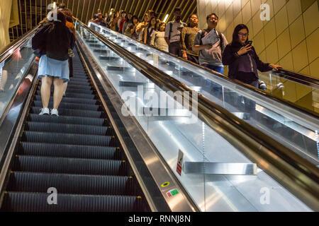 Singapore MRT Mass Rapid Transit Passengers on Escalator. - Stock Photo