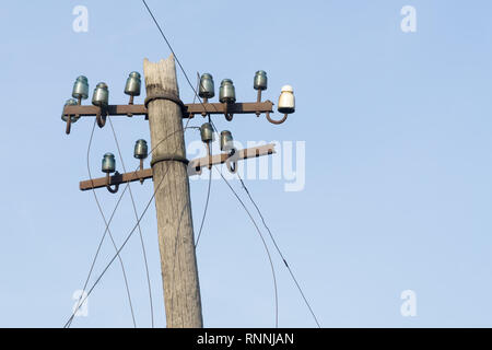 Old electric  wooden pole with glass and ceramic insulators and electric wires against blue sky. Copy space. - Stock Photo