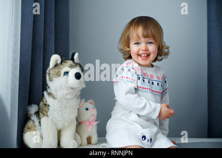 Portrait of happy little girl with curly blonde hair in casual clothes posing indoors with dog and cat toys - Stock Photo
