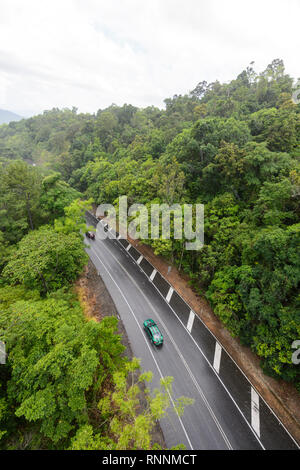 Aerial view of the road going over the Kuranda Range through tropical rainforest on a rainy day, Cairns, Far North Queensland, FNQ, QLD, Australia - Stock Photo