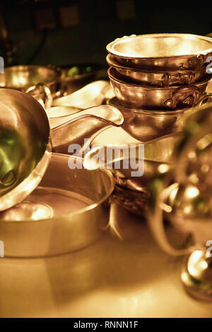 Heavy silver bowls and sauce bowls stacked in golden light. - Stock Photo