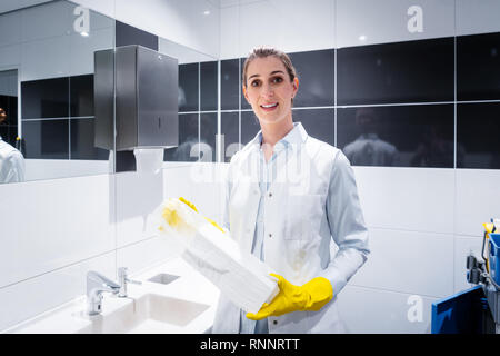 Janitor woman changing paper towels in public restroom - Stock Photo