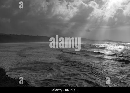 The dramatic and rugged Orgeon coastline, shot in black and white to add drama, shafts of light coming through the breaks in the clouds - Stock Photo