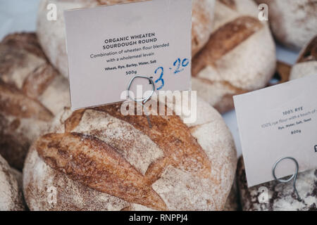 Organic wheaten sourdough bread on sale at a street market, selective focus. - Stock Photo