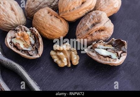 Walnuts with nutcracker, on black surface - Stock Photo