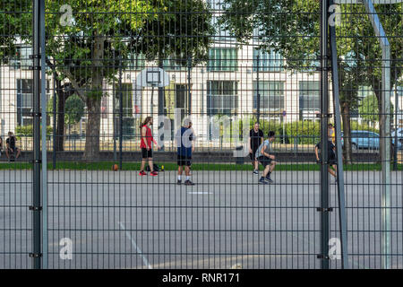 Budapest, Hungary, July 5: Young people playing basketball on a fenced urban sports ground in Budapest, July 5, 2018. - Stock Photo