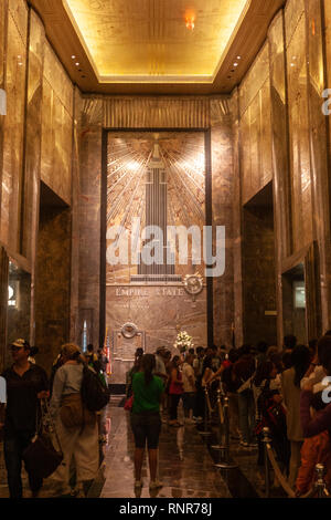 Cue of tourists in Empire State Building lobby and elevators Art Deco skyscraper in Midtown Manhattan,, New York City, USA - Stock Photo