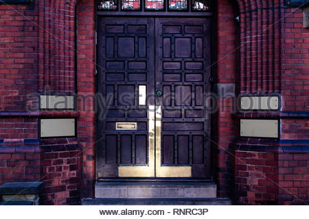 Old wooden doors with 4 blank golden plaques at the side on a brick wall. - Stock Photo