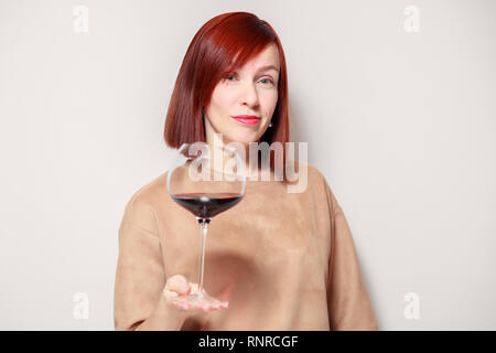 Young beautiful redhaired girl sommelier with bright lipstick on white background is smiling and holding glass of red wine at professional blind tasti - Stock Photo