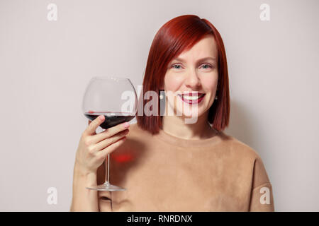Young beautiful redhaired girl sommelier smiling and holding glass of red wine at professional blind tasting sommelier competition. Concept alcoholism - Stock Photo