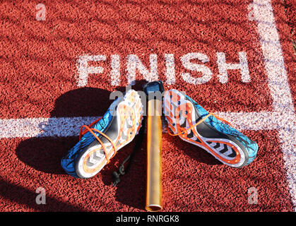 The finish line of a track with a stopwatch, baton and a pair of racing spikes on it. - Stock Photo