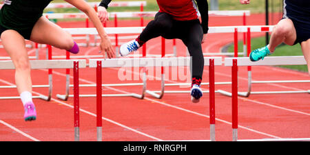 Three high school girls are racing the hurdles at a track and field competition - Stock Photo