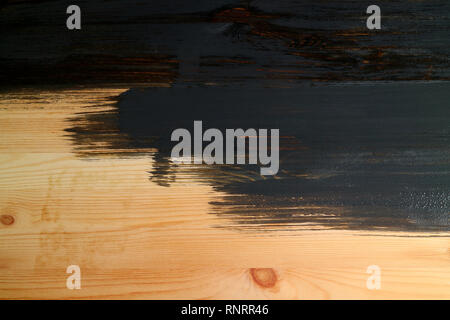 Work in progress of a wooden plank painting with dark grey paint - Stock Photo