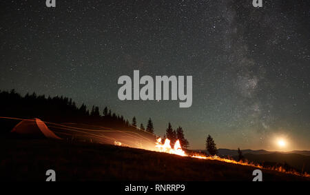 Silhouette of friends tourists resting together around campfire near camp and tent at night in the mountains. On background forest and beautiful night starry sky full of stars, moon and Milky way. - Stock Photo