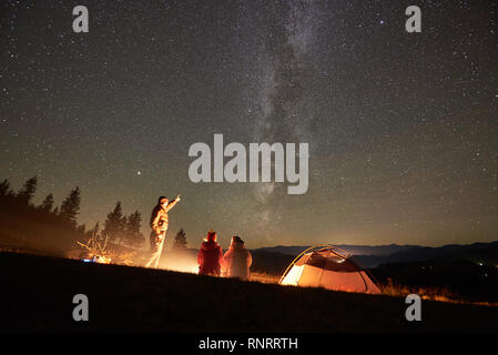 Happy friends hikers having a rest together around campfire beside camp and tourist tent at night in the mountains. Man pointing at incredibly beautiful night starry sky full of stars and Milky way. - Stock Photo