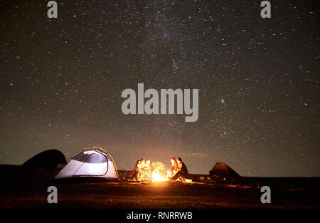 Young friends hikers having a rest together around bonfire beside camp and glowing tourist tent at night in the mountains. On background beautiful night starry sky full of stars and Milky way. - Stock Photo