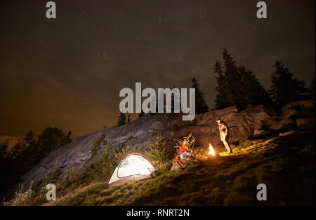 Night summer camping in the mountains. Happy couple travellers having a rest together beside campfire and illuminated tourist tent. On background big boulder, forest and beautiful night starry sky. - Stock Photo