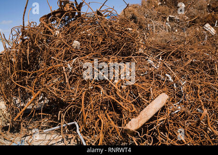 Pile of assorted rusted metal rods and pipes in scrap metal recycling yard - Stock Photo