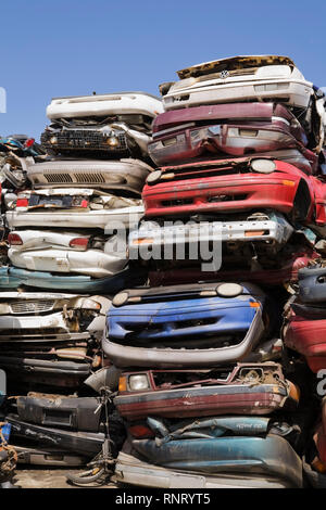 Stacked and crushed automobiles at a scrap metal recycling junkyard - Stock Photo