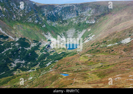 Panoramic view of a mountain lake in a rocky mountain valley. Serene lake Berbeneskul, Carpathians, Ukraine. Great view of Montenegrin Range above bea - Stock Photo