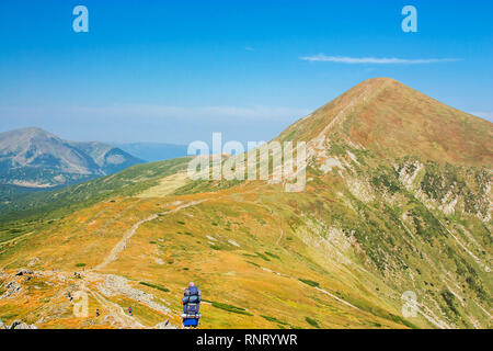 Tourists on the trail in the mountains. Panoramic view of the rocky mountains of the Carpathians, Ukraine. Beautiful view of the Montenegrin ridge. - Stock Photo
