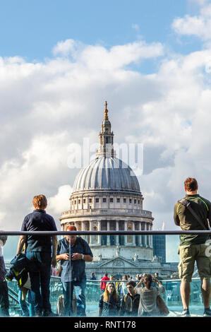Tourists taking pictures of St. Paul's Cathedral on the Millennium Bridge, London, UK - Stock Photo