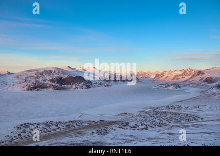 Overlooking the town of Pangnirting. This is the entire town visible soutth (left) to north during sunset in winter. - Stock Photo