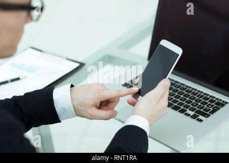 close up. a businessman uses a smartphone in the workplace - Stock Photo
