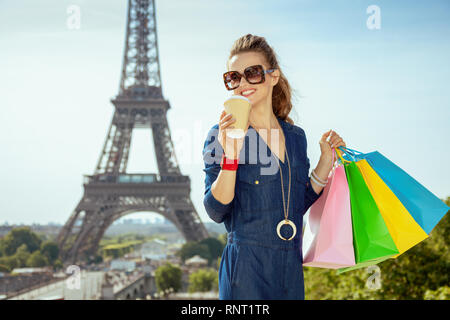 smiling elegant traveller woman in blue jeans overall with shopping bags and coffee cup at Trocadero overlooking Eiffel tower in Paris, France. - Stock Photo