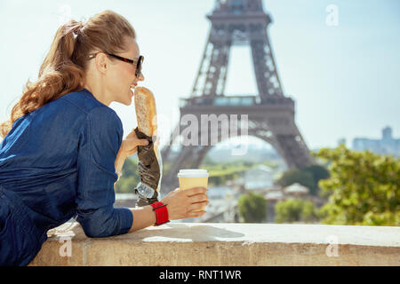 smiling elegant traveller woman in blue jeans overall with coffee cup eating baguette having excursion against clear view of the Eiffel Tower in Paris - Stock Photo