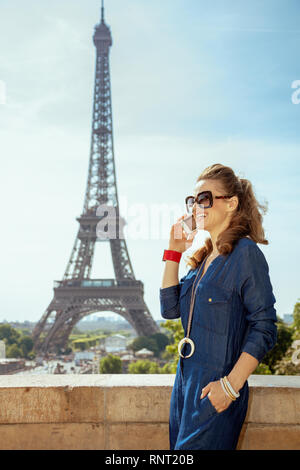 smiling elegant tourist woman in blue jeans overall in Paris, France speaking on a mobile phone. - Stock Photo