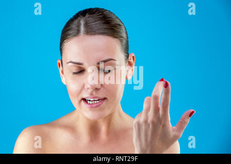 The pretty European young angry brown-haired woman with healthy clean skin, screaming, waving her arms, on a blue background. Emotions concept. - Stock Photo