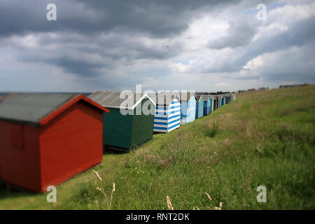 Brightly coloured beach huts beneath Tankerton Slopes, Whitstable, Kent, UK. Photographed using a perspective-control lens. - Stock Photo