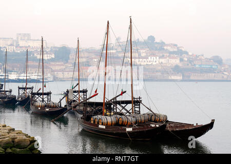 Porto, Portugal - March 31, 2012: Traditional Rabelo Boats of the River Douro, anchored in a pier of Gaia, twin city of Porto, in a foggy morning - Stock Photo