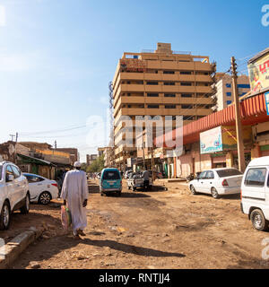 Khartoum, Sudan, February 5. 2019: Unpaved side street with a skyscraper and small sales huts and stalls as well as cars and pedestrians in the middle - Stock Photo