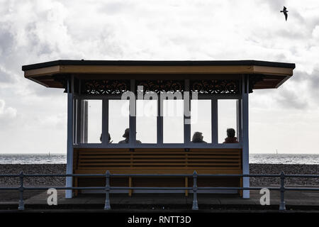 People sat on victorian shelter, Southsea, Portsmouth, Hampshire, UK - Stock Photo
